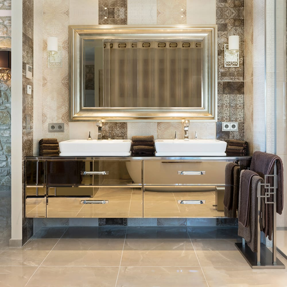 statement furniture, bronze mirrored vanity unit, 2 white basins, gold taps, mirror above
