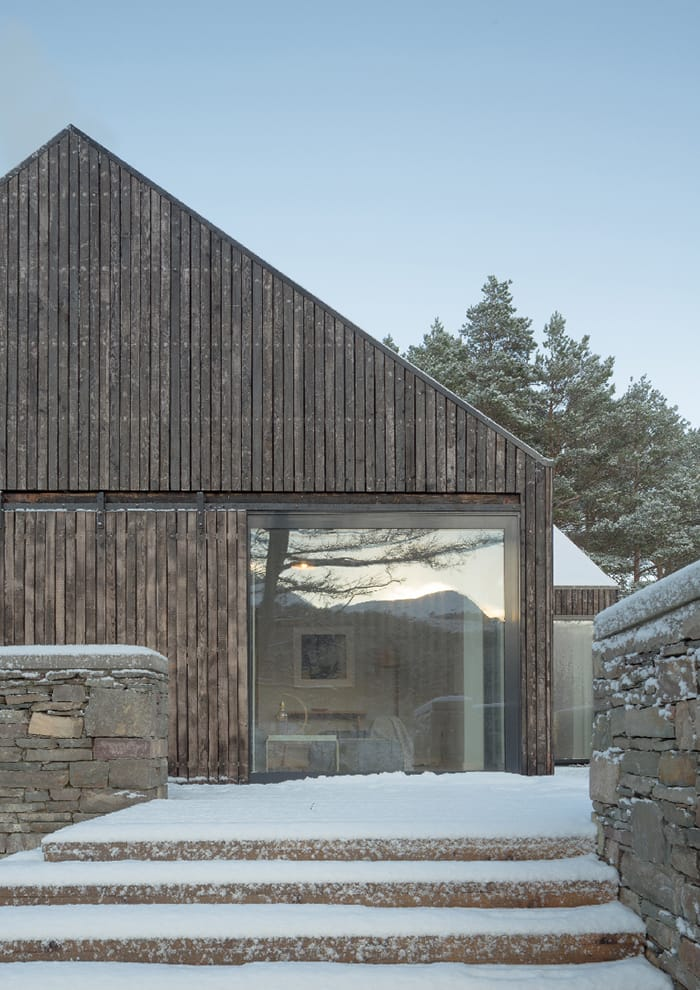 Lochside House exterior in the snow, showing large, full height picture window, RIBA Awards 2018