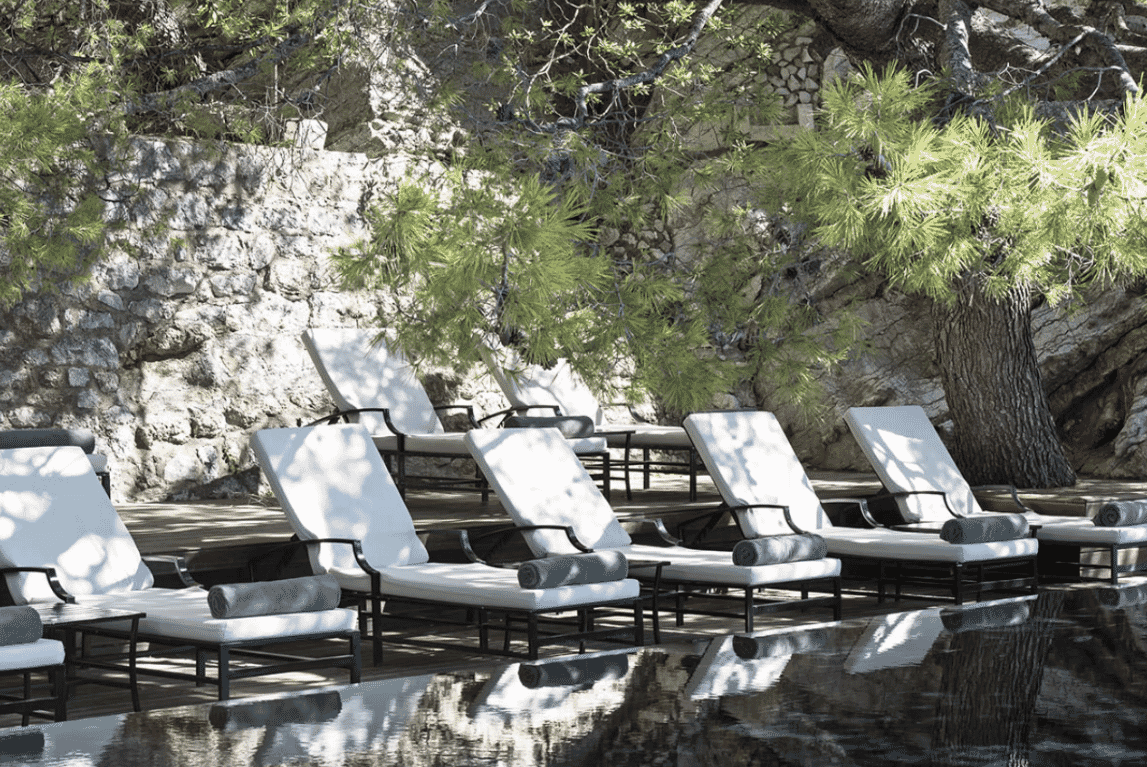 Aman Sveti Stefan hotel, cliff pool with stone wall, pine trees and sun loungers