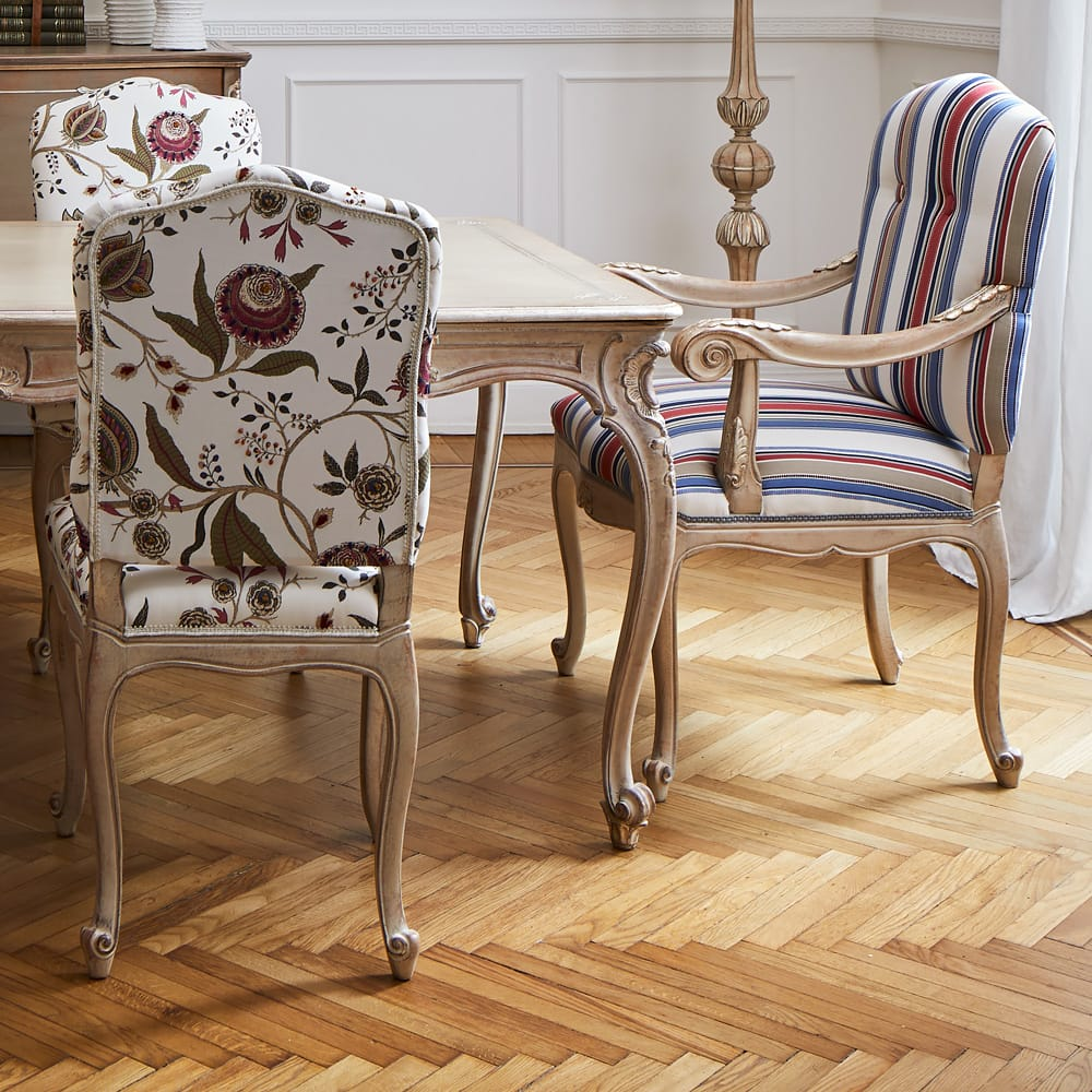 Impress the guests, classic carved wooden dining chairs, one in stripy fabric, others floral