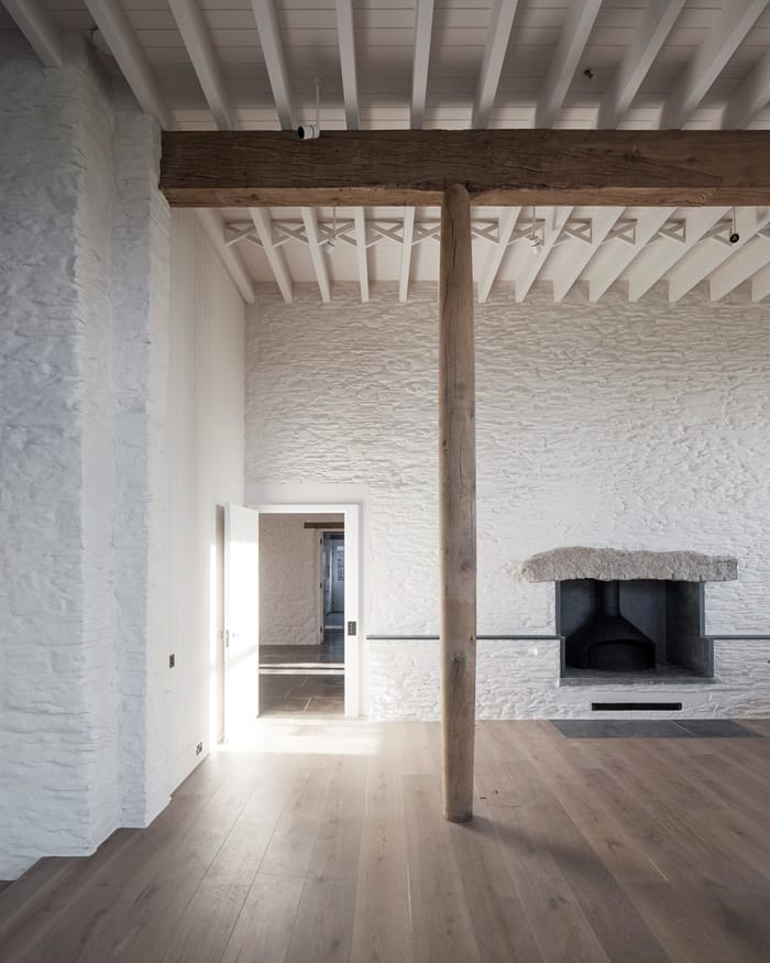 Coastal House living area with wooden floor, pillar, open fireplace, white painted stone walls RIBA Awards 2018