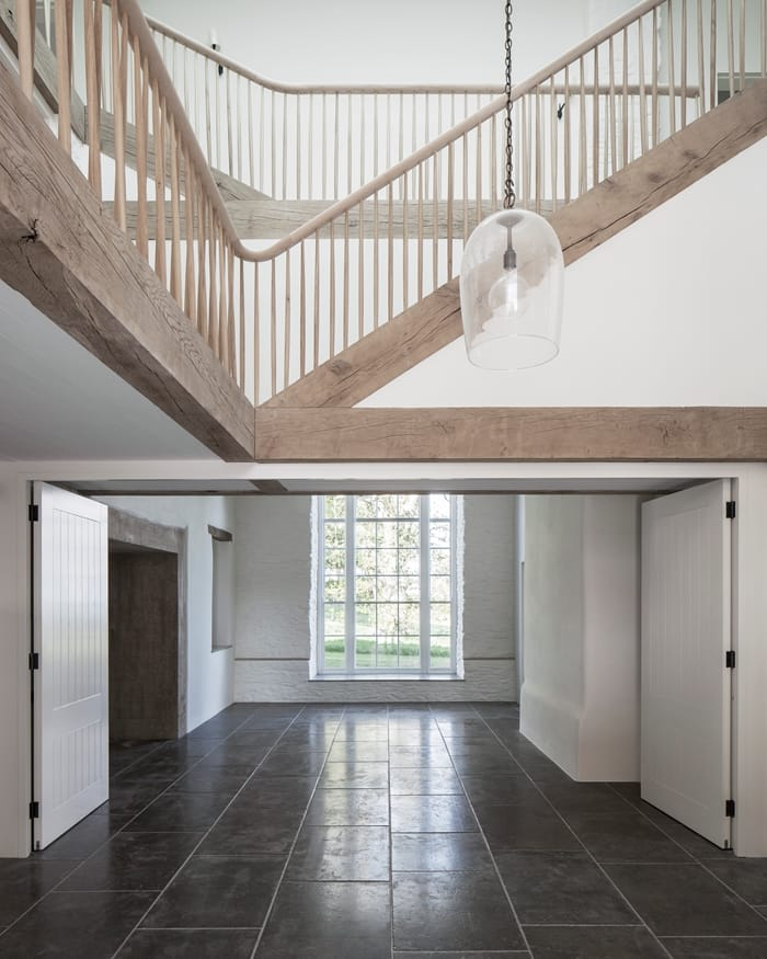 Coastal House living space with full height window and wooden staircase RIBA Awards 2018
