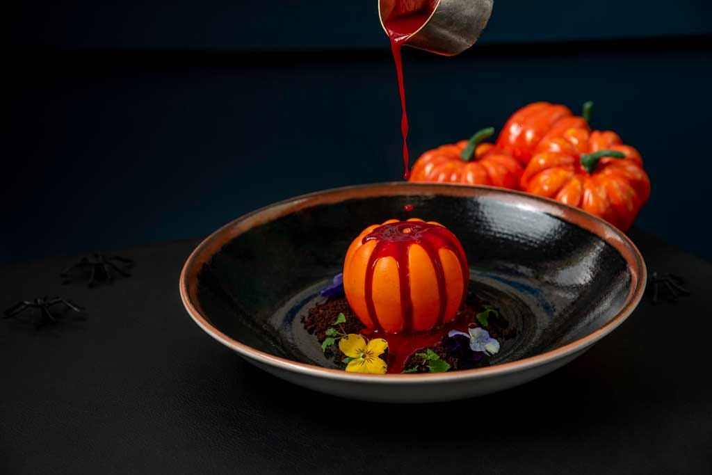 Halloween decor, pumpkin shaped dessert with blood red sauce