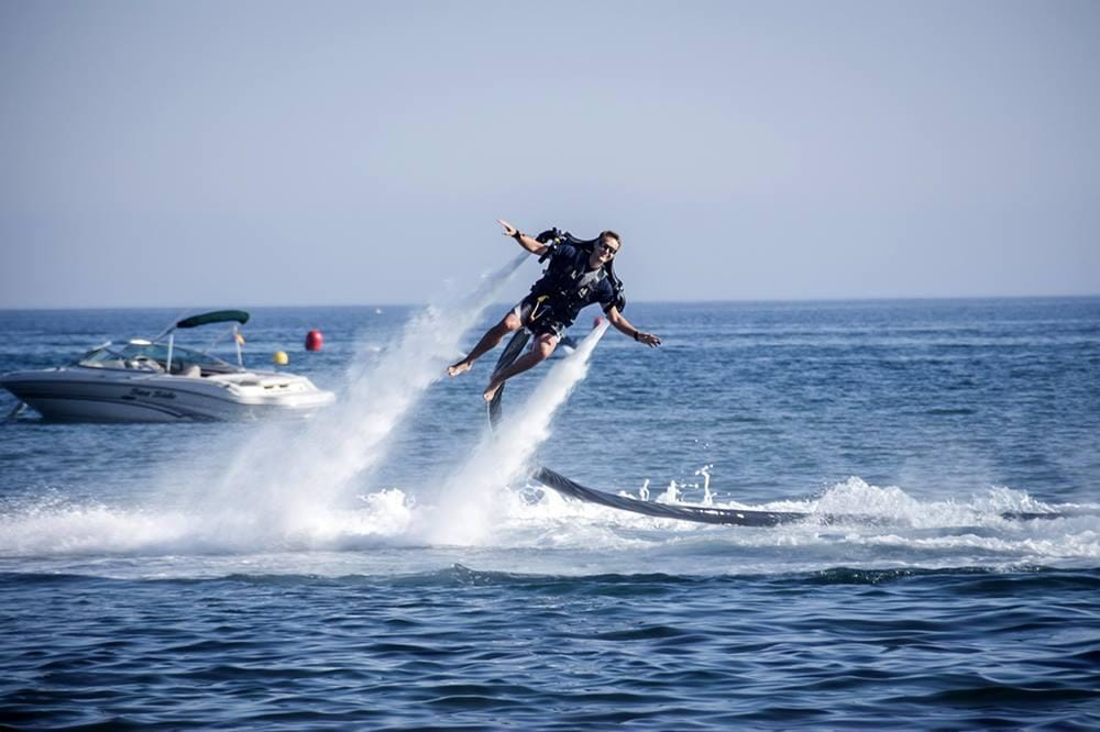 Man with Jetpack, flying above the sea, motorboat in background, yacht toys