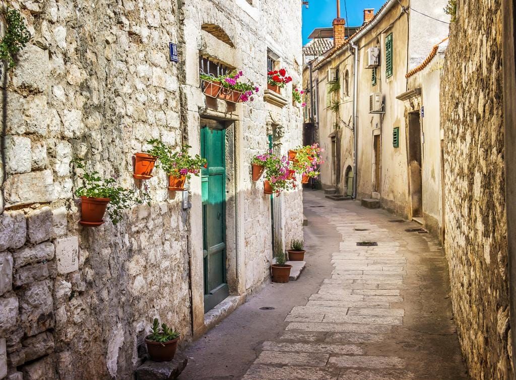 Narrow cobbled street in Kotor Old Town, Montenegro, with stone houses and flower pots on walls