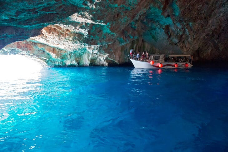 Lustica Peninsula Montenegro, inside the Blue Cave with iridescent blue water and one boat