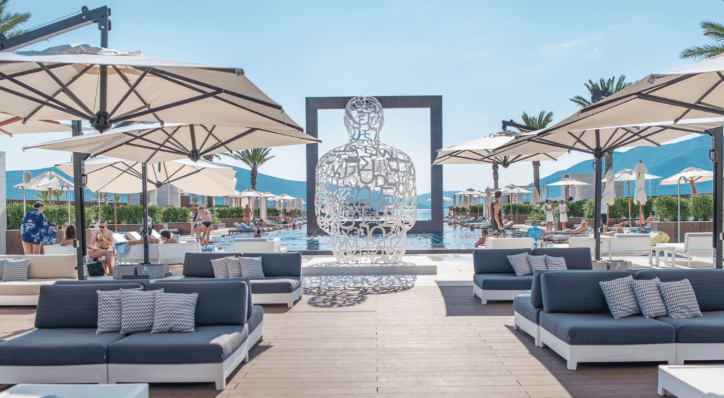 Regent Porto Montenegro hotel, yacht club pool with modern sculpture, umbrellas and sun loungers