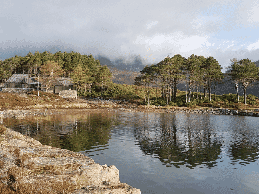 Lochside House on waterside with forest, mountains and clouds in background RIBA Awards 2018