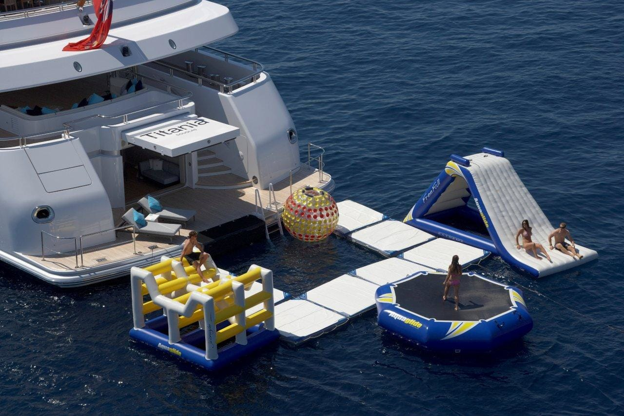 Yacht toys, back of Titania super yacht showing sea pool, zorb, slide, trampoline and obstacle