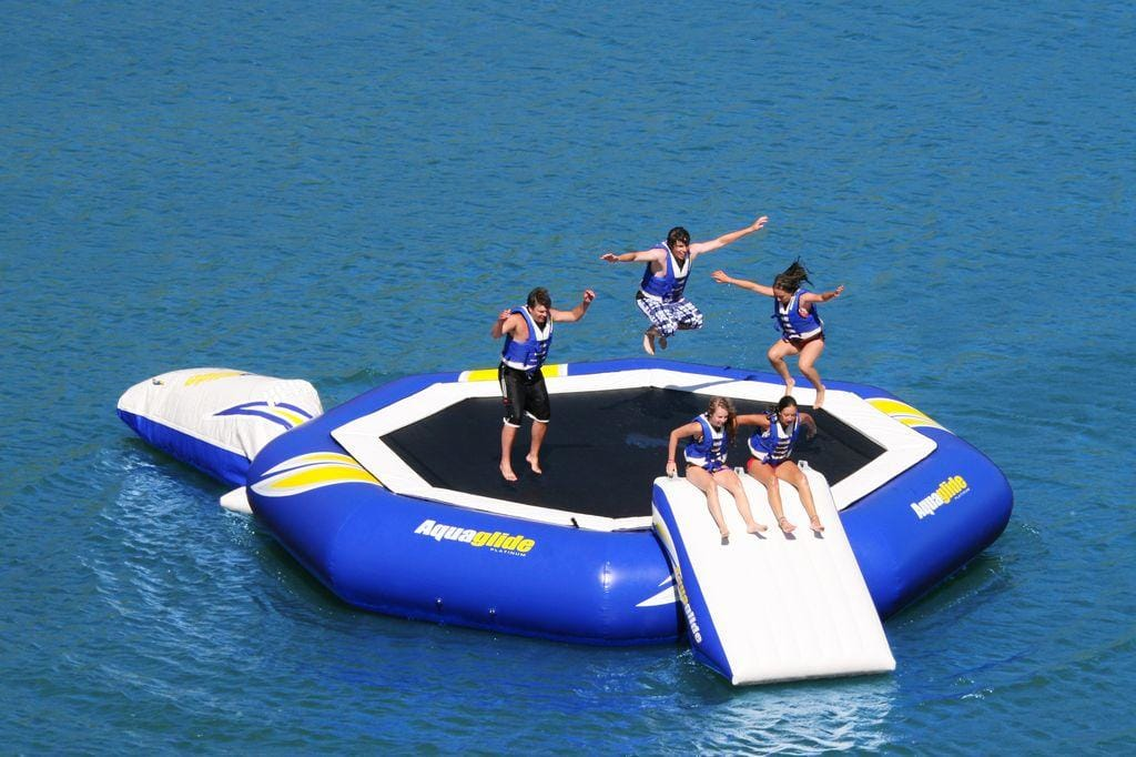 Yacht toys, connected trampoline with slide and air cushion, people bouncing and sliding into the sea