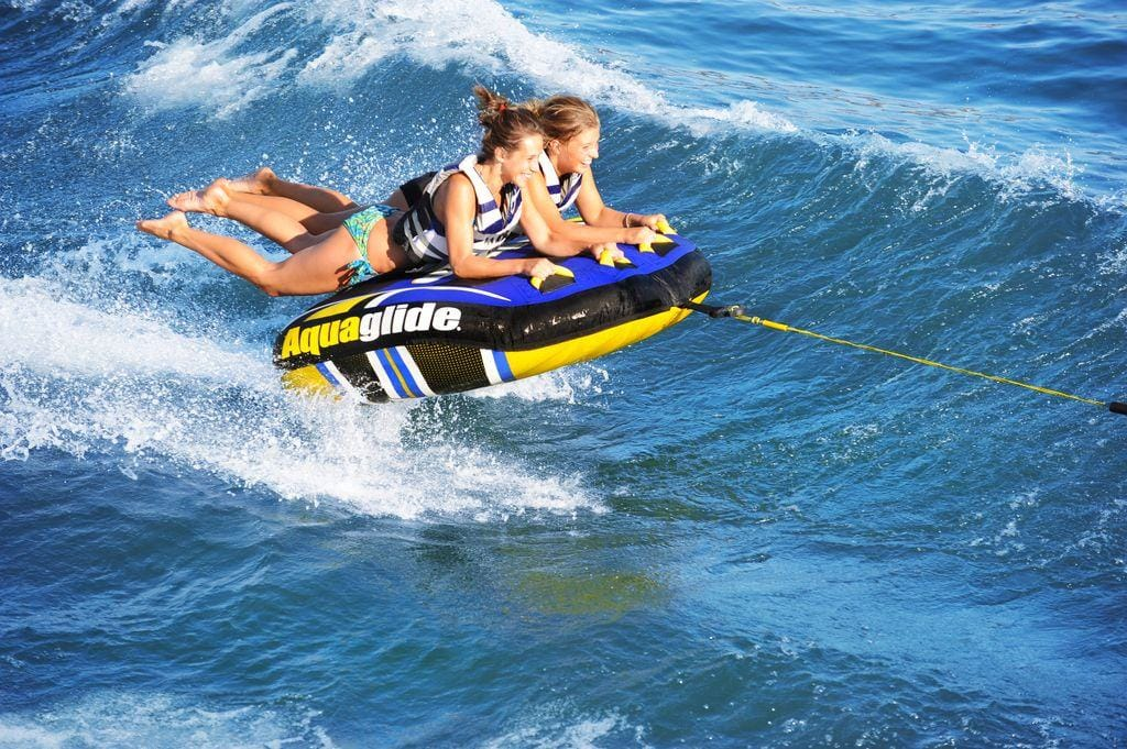 Yacht toys, inflatable cushion being towed behind a speedboat, two people hanging on