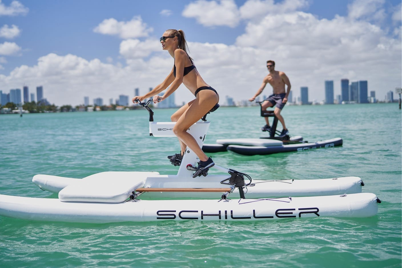 Yacht toys, woman in foreground on a Schiller sea bike, man and city skyline in background