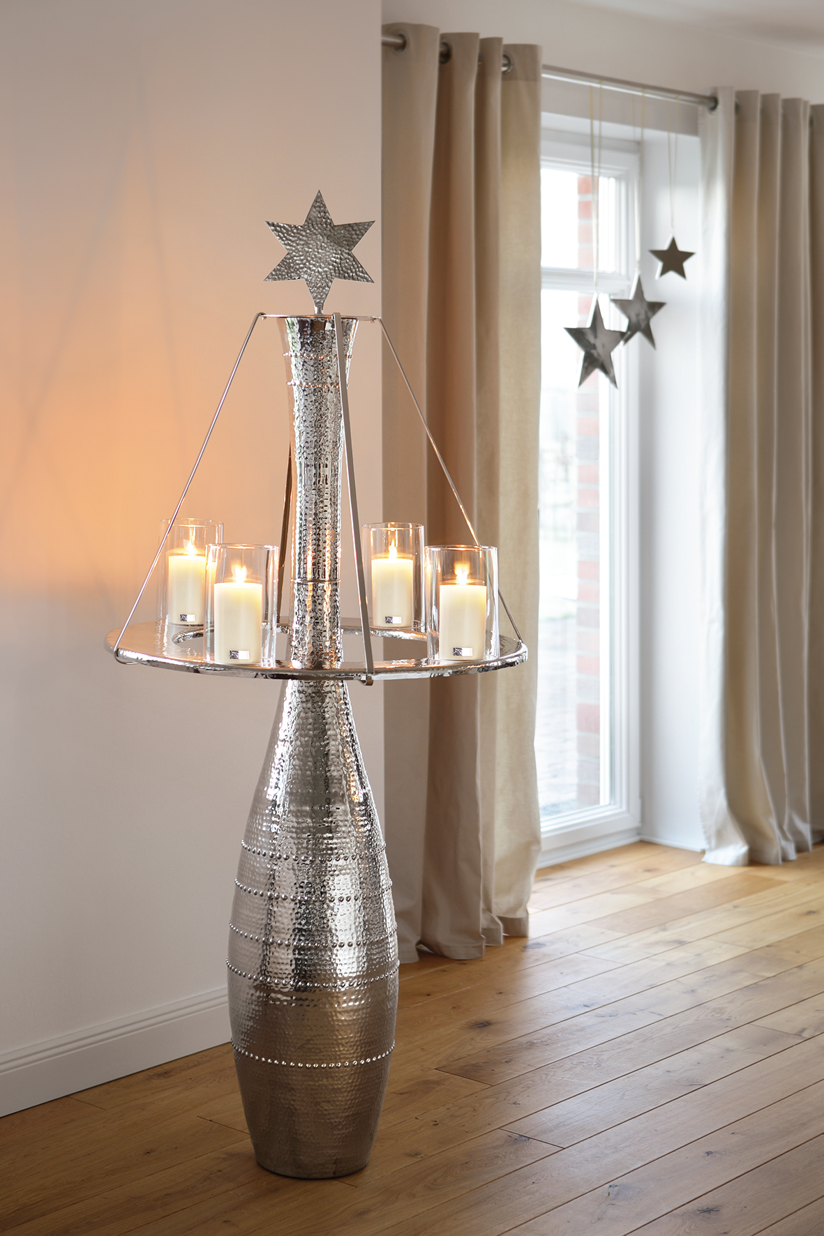 Christmas dining, tall nickel candlestick with star and hoop decoration