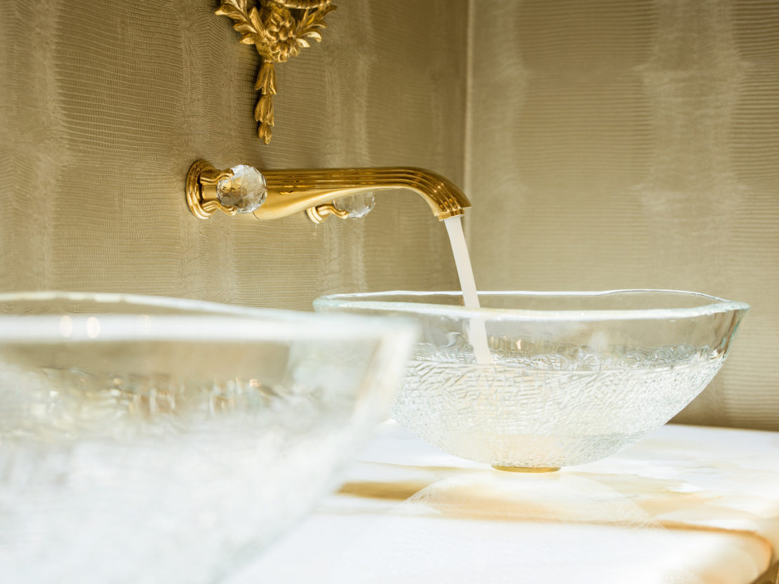 under the stairs, powder room with embossed clear glass basins, gold tap with crystal handles