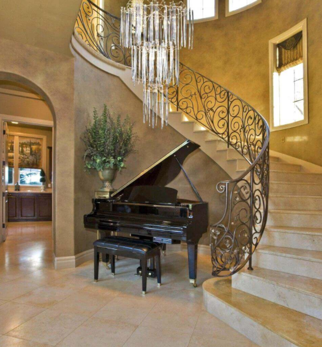 ornate staircase with baby grand piano