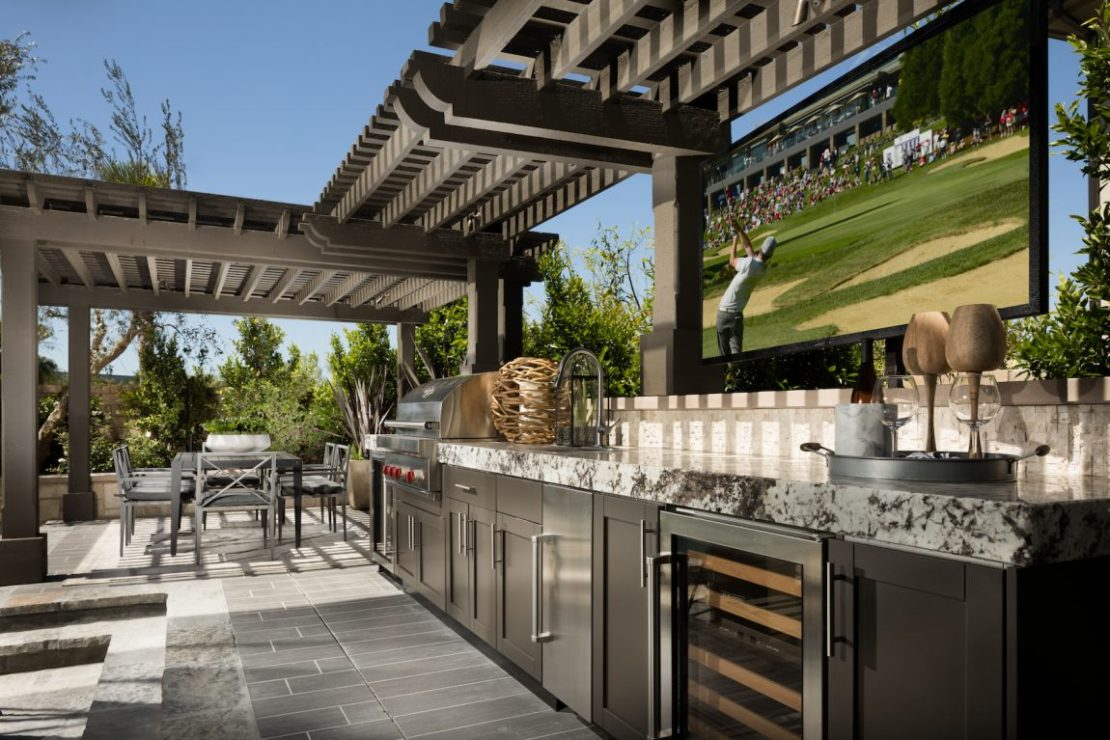fantasy garden outdoor kitchen with marble tops, wine fridge, stainless steel cupboards, T.V.