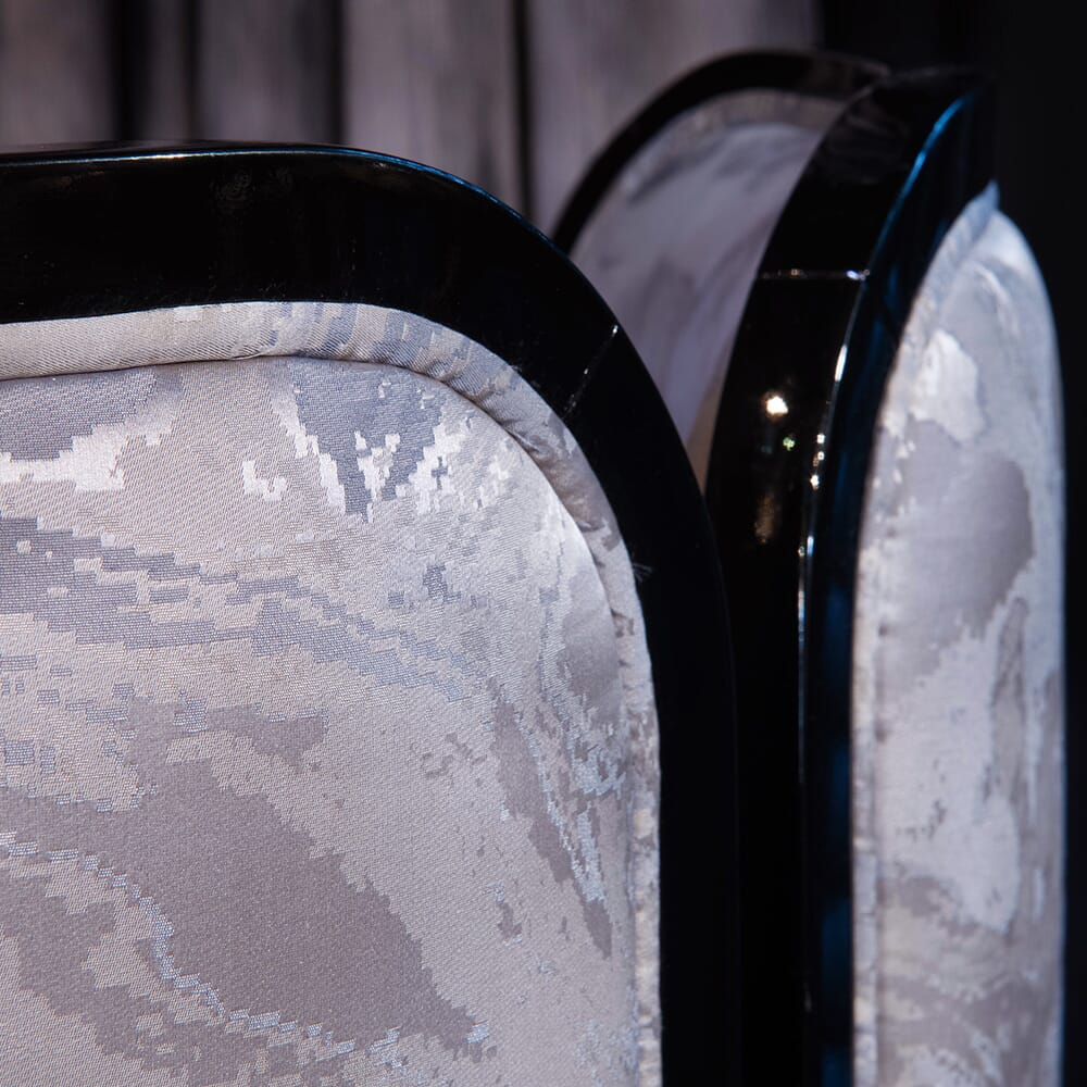 black lacquer detail and jacquard fabric on back of luxury dining chair