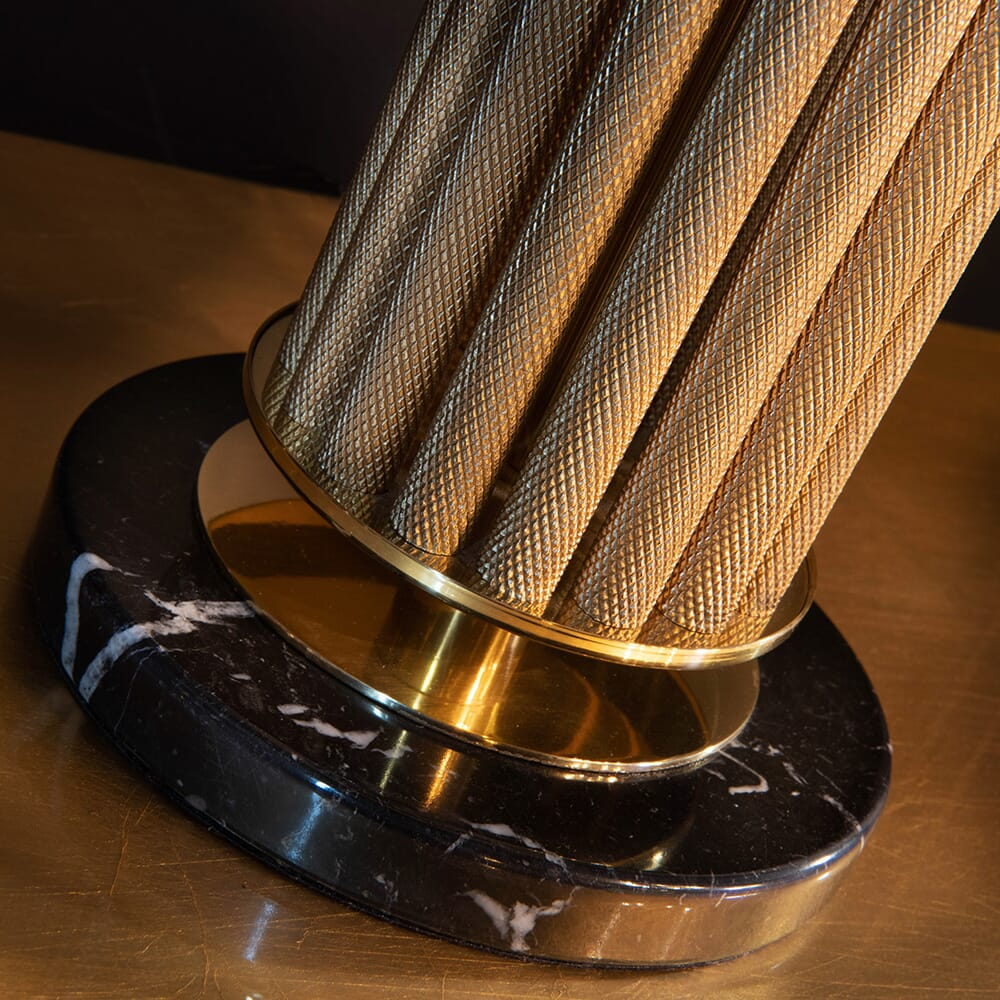 luxury furniture, detail of lamp base with textured, gold metallic poles and black marble base