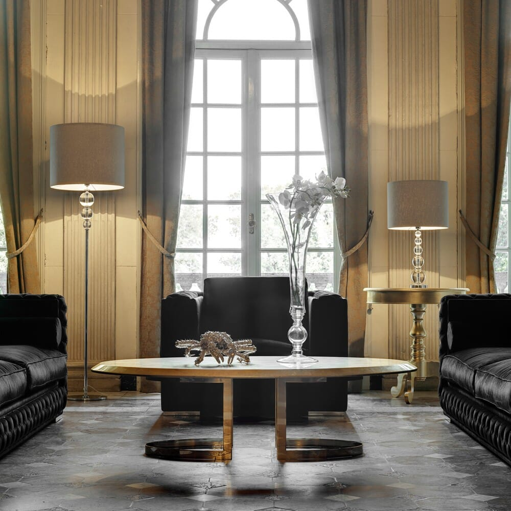 eclectic glamour interior design trend, classic room with high windows, tiled floor, and contemporary oval coffee table