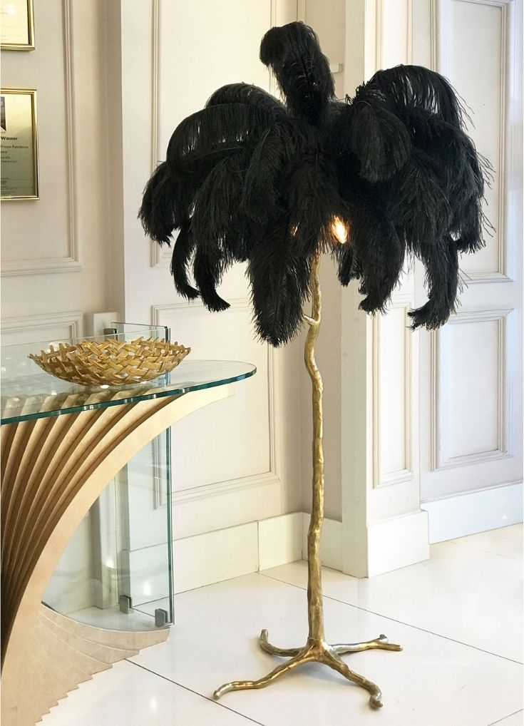 Luxury gift guide 2020. Fabulous, quirky floor lamp with gold, tree-like stem and flamboyant black feather top