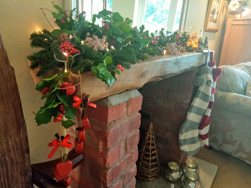 Christmas mantelpiece with foliage, berries, lights and wooden hanging apples