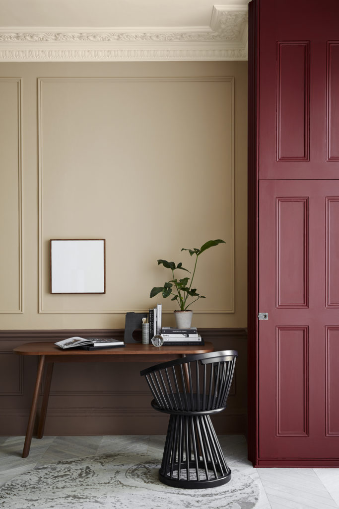 desk space with warm neutral walls and shutters in deep red