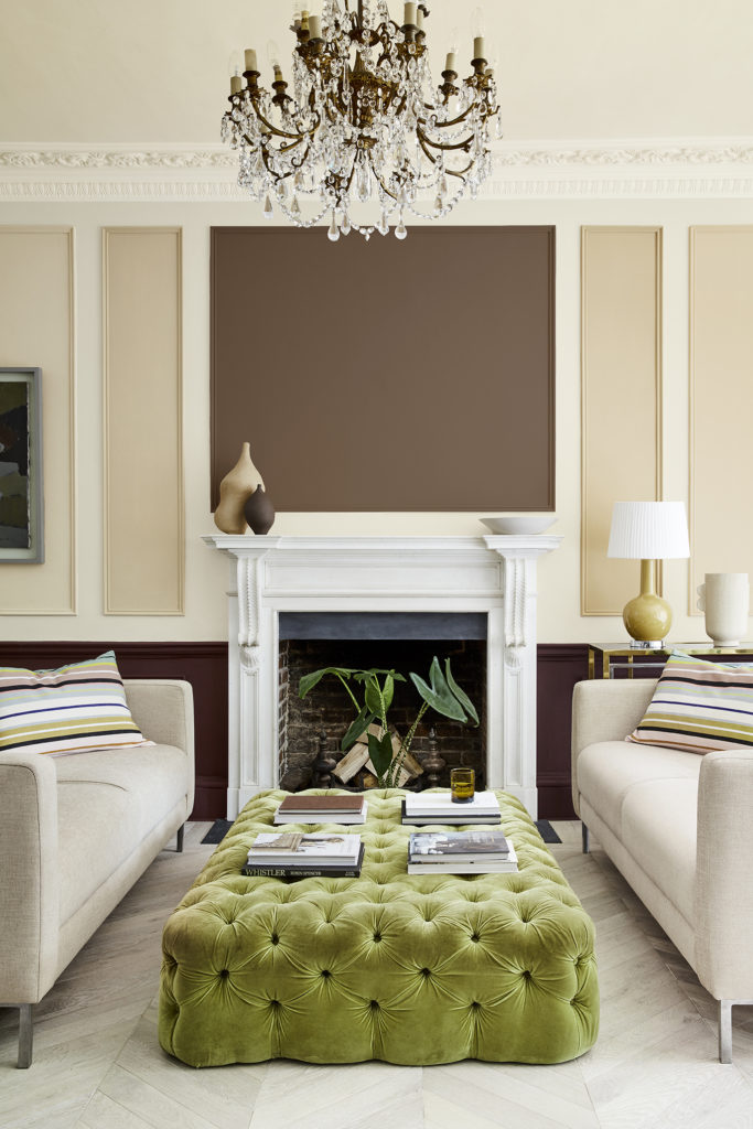 a calm colour scheme with neutral walls and sofas and an accent of lime green footstool